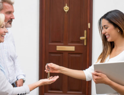 older couple receiving keys to new home from attractive female real estate agent