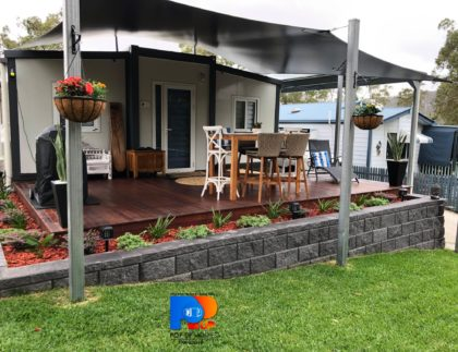 established tiny / small home with deck, block retaining wall and outdoor furniture and bbq