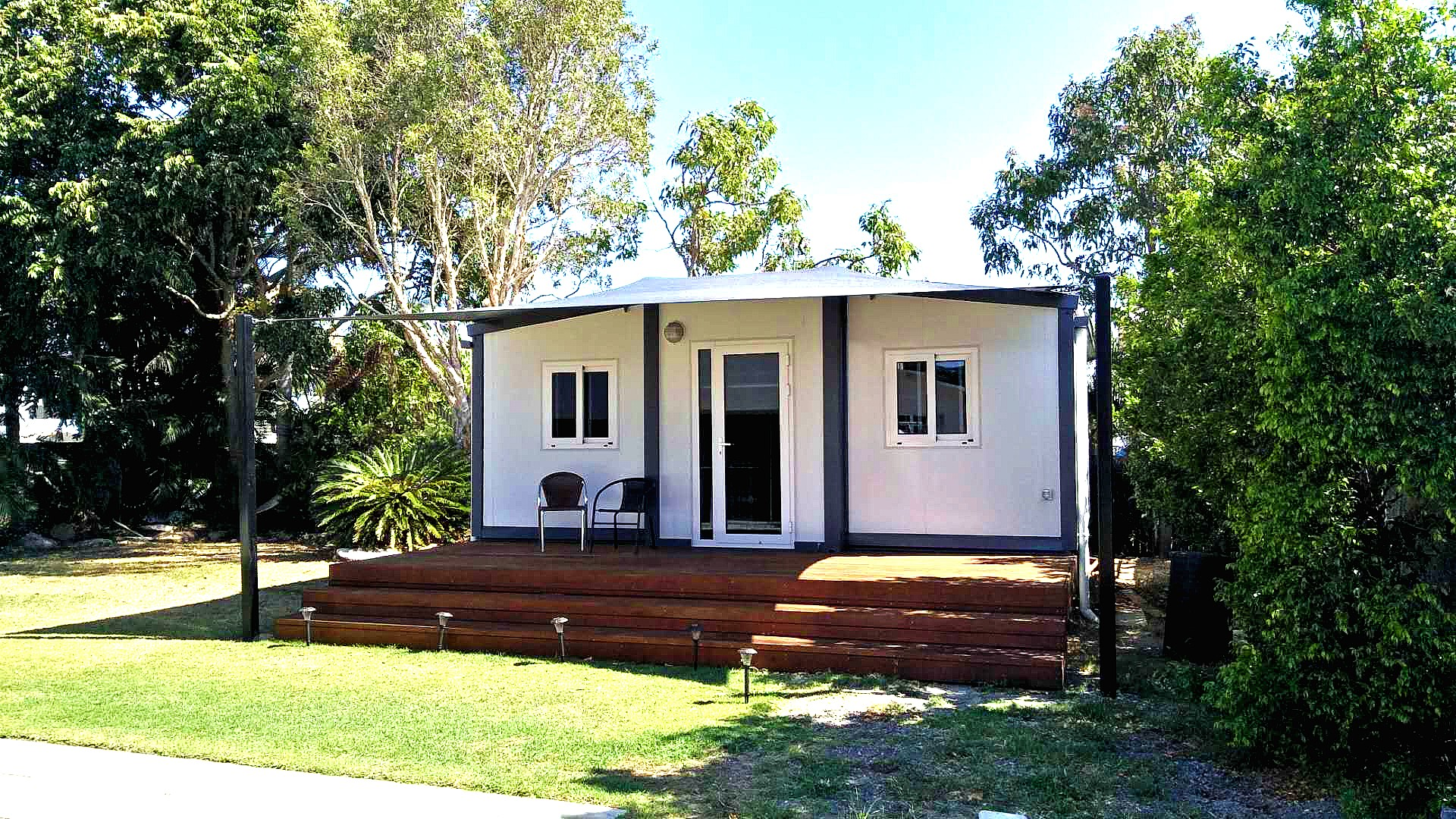small / tiny home installed into backyard bathed in morning sunshine and cool shade