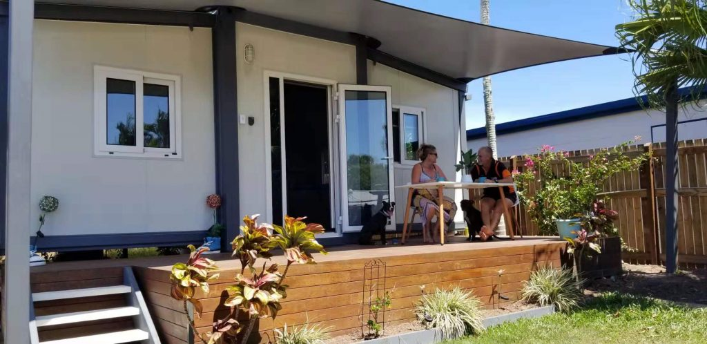 couple discussing business on small table sitting on verandah of a tiny small home
