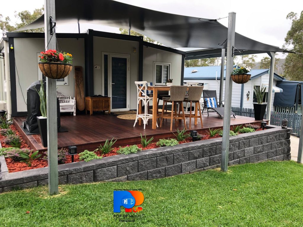 Completed tiny / small home with deck and block grey retaining wall. Outdoor Furniture and BBQ