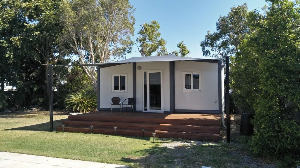 Tiny Home with deck steps with sale in back yard