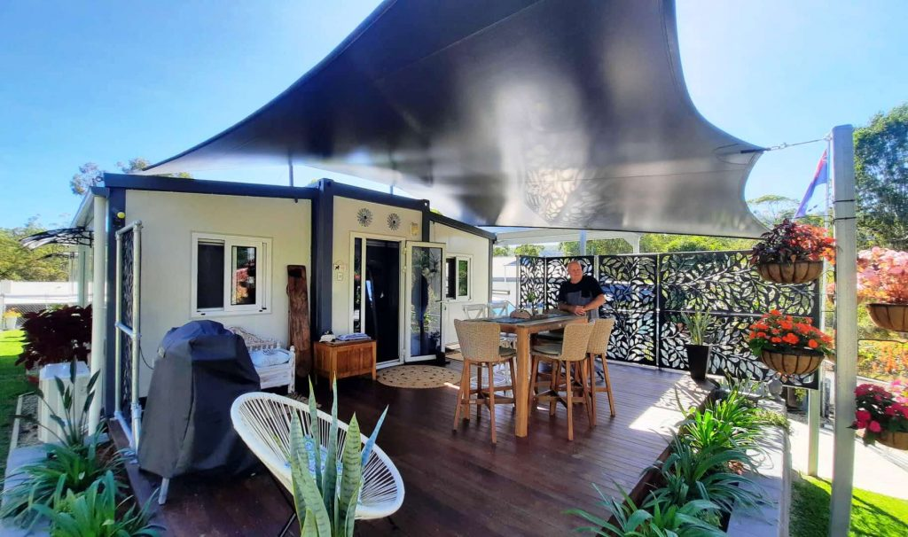 man enjoying fully set up tiny home, landscaped, bbq, deck, awning - awesome